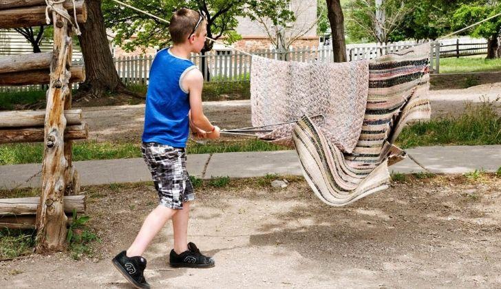 A boy hitting a rug on a washing line