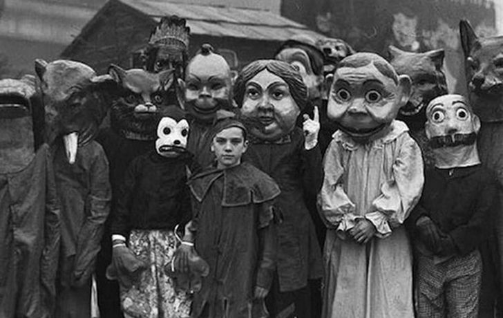 Greyscale photo of a group of people wearing horrifying costumes.