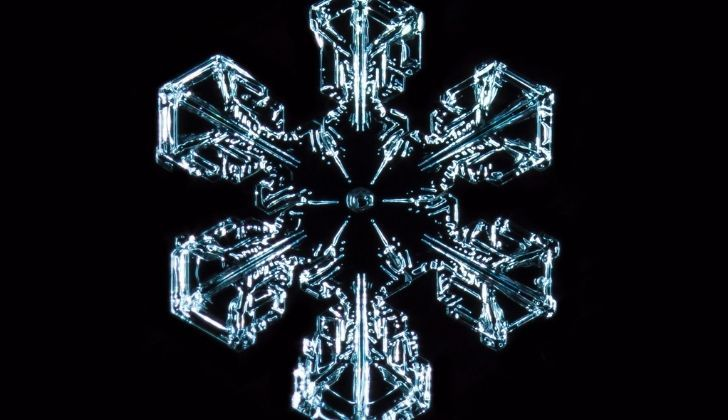 Closeup of one snowflake against a dark background