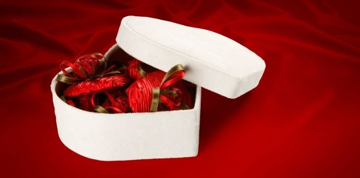 A white heart shapes box with chocolate inside individually wrapped in deep red paper
