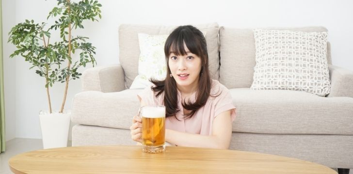 A woman having a pint of beer at home