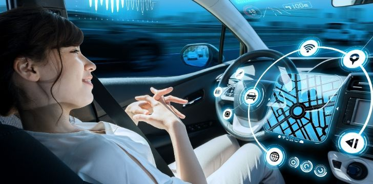A woman sitting in her car with lots of pictures on the steering wheel showing a driverless cars possibilities