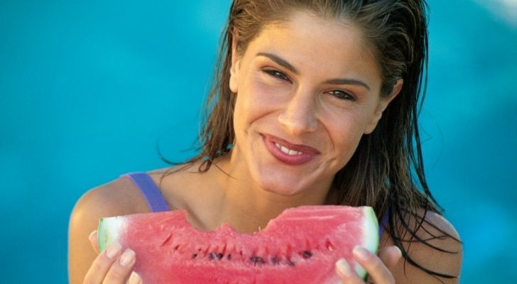 A healthy woman smiling and eating a delicious slice of watermelon