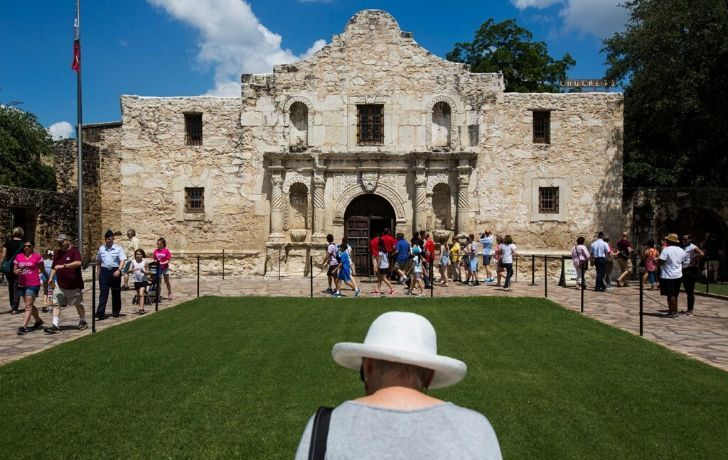 The Alamo Mission building with tourists outside the entrance
