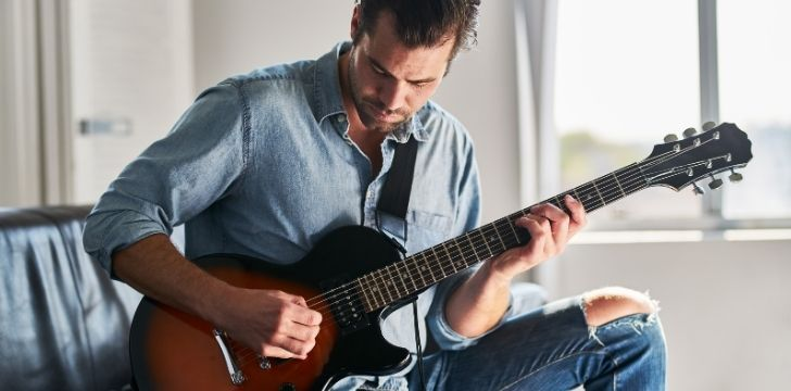 A man learning to play a guitar sitting on the sofa