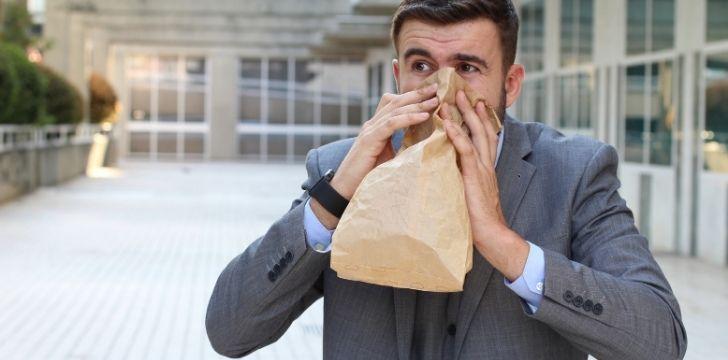 A man breathing through a paper bag