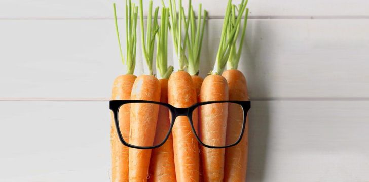 Carrots on a woodern background wearing glasses.
