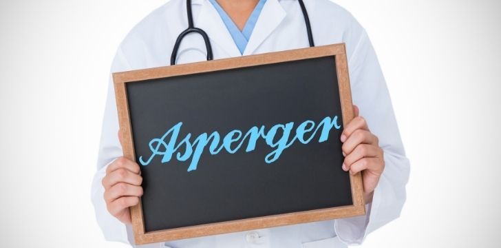 A doctor holding a chalkboard that reads Aspergers on it