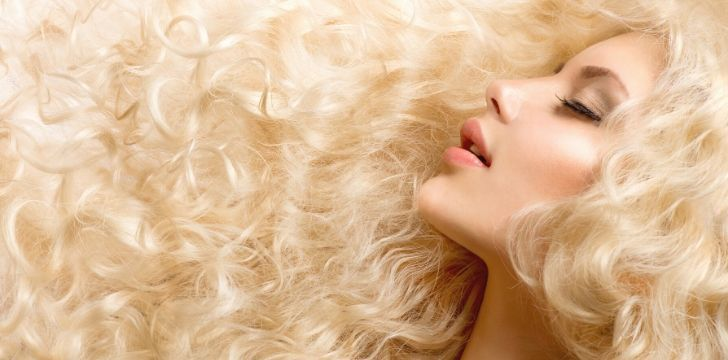 A woman with long wavy healthy blonde hair