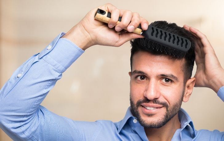 A man brushing his hair and smiling