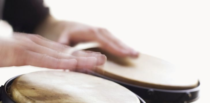 Bongo drums being played with both hands.