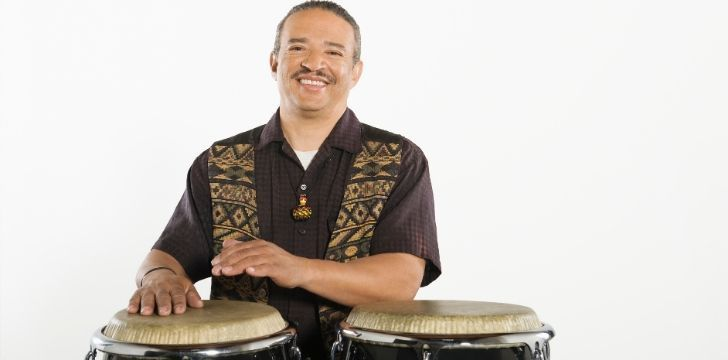 A man smiling behind a pair of Bongo drums.
