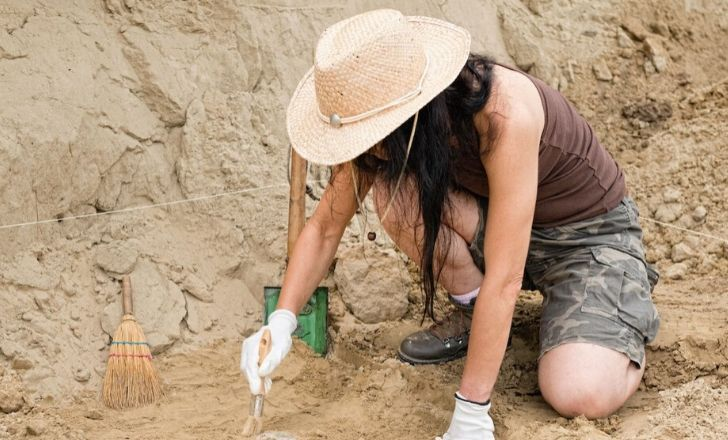 Archeologist digging in the ground.