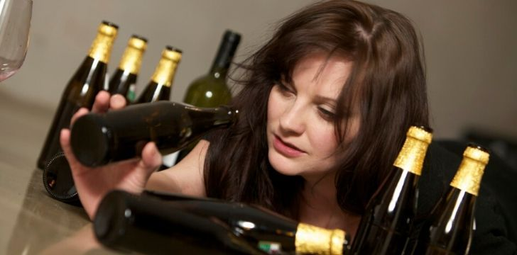 A woman looking for the last drop of wine in a bottle to cure her hangover