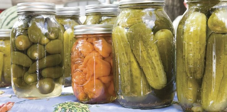 A mix of jars with pickles and pickled carrot
