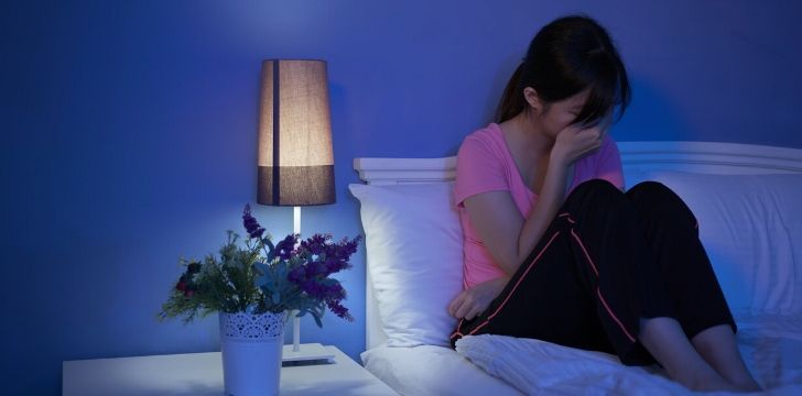 A depressed woman in bed with her hand over her face