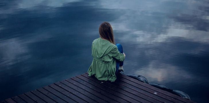 A depressed woman sitting on a dock looking over a lake