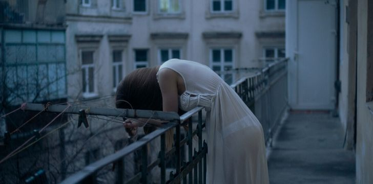 A depressed women on a balcony