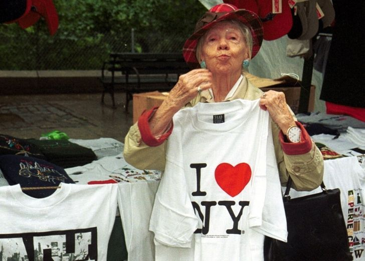 "An older lady holding up a t-shirt that reads ""I Heart NY"""
