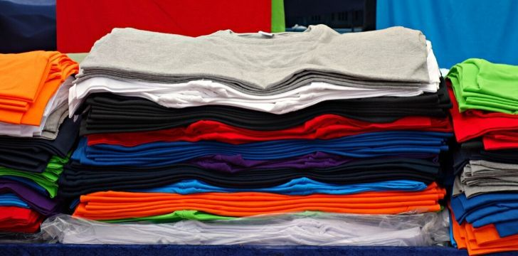 A big pile of different colored t-shirts