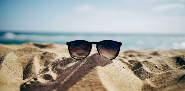 A pair of Ray Ban sunglasses on sand at the beach with the ocean behind