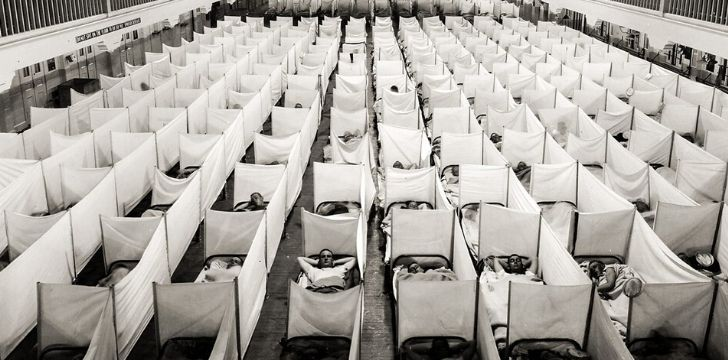 A large hall filled with beds of sick patients