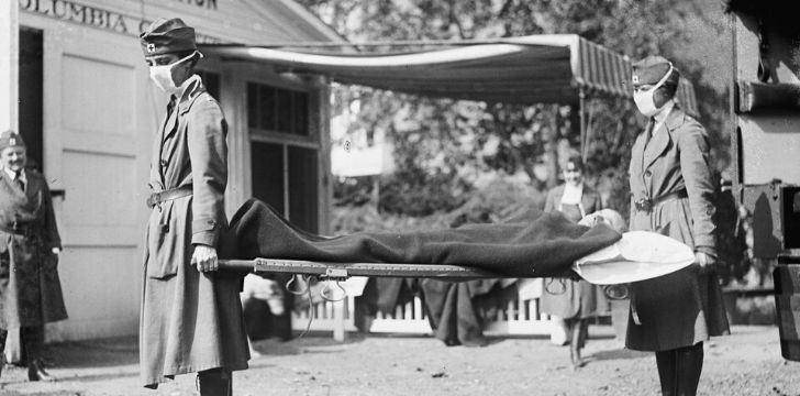 Two nurses carrying a sick man on a stretcher