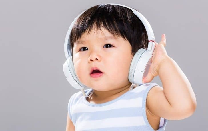 A baby listening to music on headphones