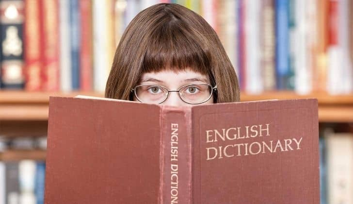 a girl with glasses peering over the top of an open English dictionary