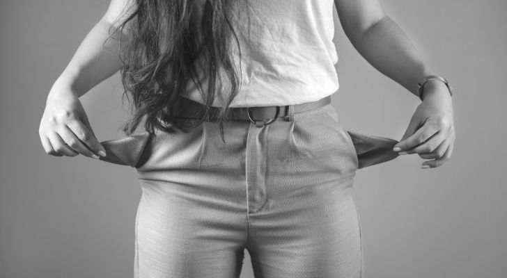 A woman pulling out her empty pockets in her jeans