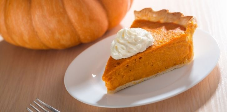 A slice of pumpkin pie with a dollop of cream on top