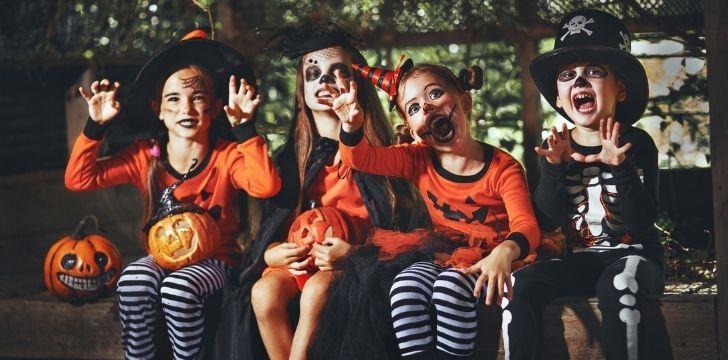 Children sitting in Halloween costumes