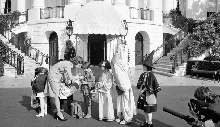 A black and white photo showing children dressed Halloween costumes outside the White House