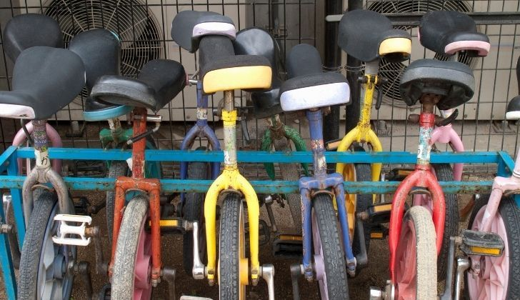 Rows of unicycles against a metal rack