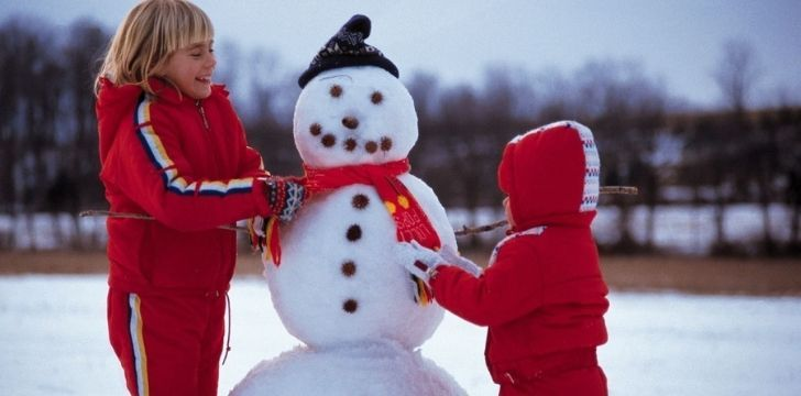 Two kids building a snowman
