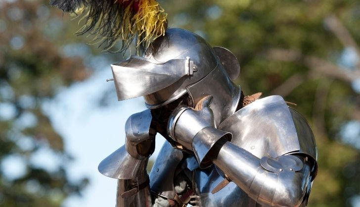 Someone wearing a full metal Medieval knight outfit