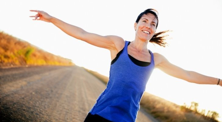 A runner with her hands open wide and smiling