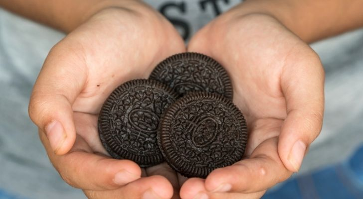 Someone with a bunch of yummy Oreos in her hands