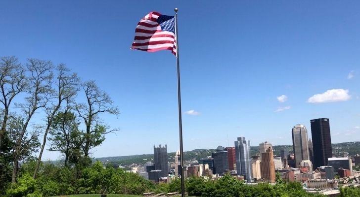 The USA flag with Pittsburg in the background