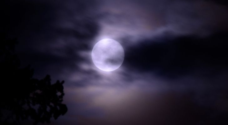 A picture of the moon from Earth with a chilly cloudy sky