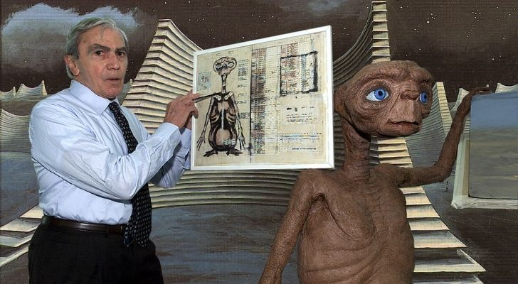 A picture of Carlo Rambaldi holding an illustration of E.T.