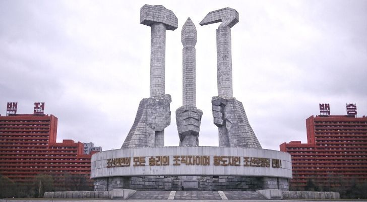 A famous landmark in North Korea showing three hands holding tools