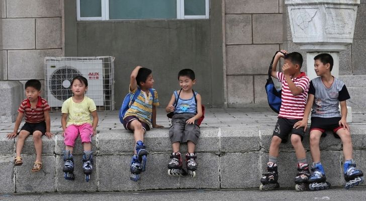 Children sitting on a wall wearing roller-skates