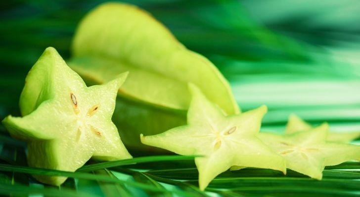 A green star fruit sliced down the middle
