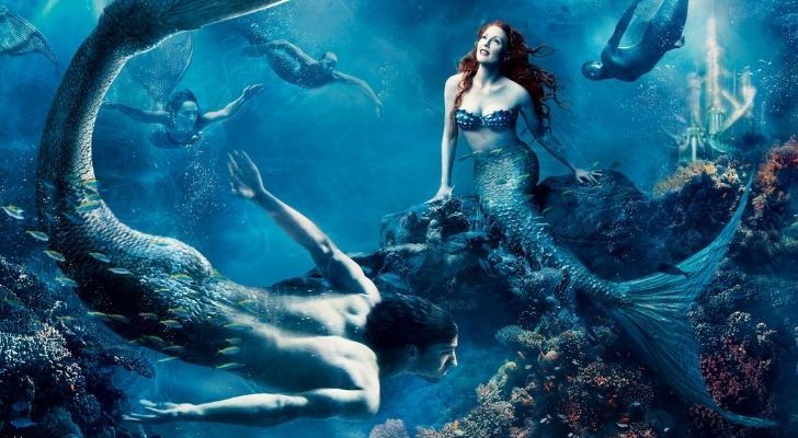 A mermaid sitting on coral under the sea