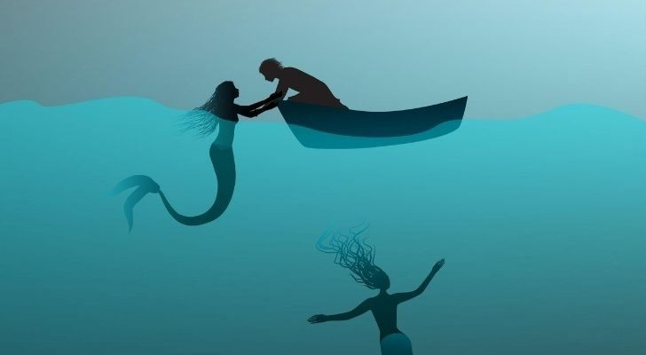 A mermaid pulling a sailor into the seas