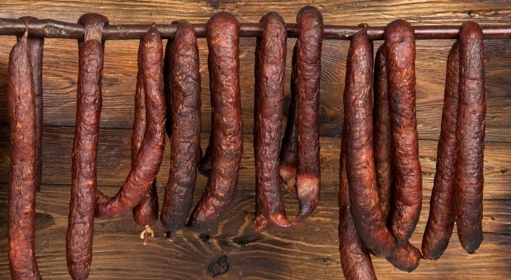 Lots of brown sausages hanging from a pole
