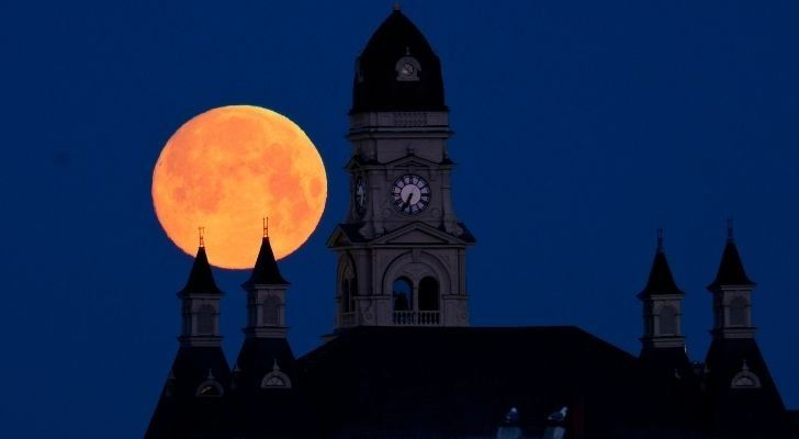 Bright worm moon in the sky behind a clocktower