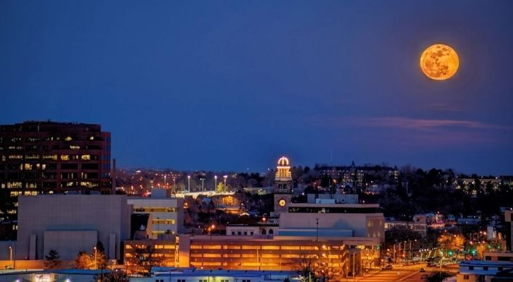An orange worm moon shining above a city