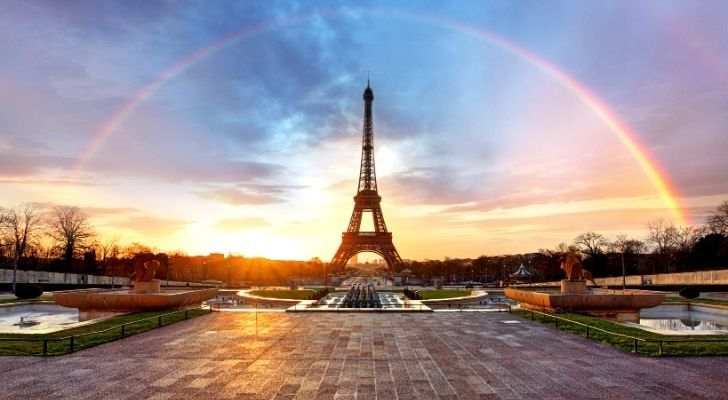 Eiffel Tower with a rainbow arched across it in the sky